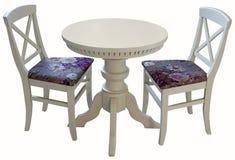 Mesa redonda de madera blanca con dos sillas Imagen de archivo