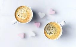 Mesa rom?ntica con dos tazas de caf? y de melcochas en forma de coraz?n rosadas Visi?n superior fotografía de archivo