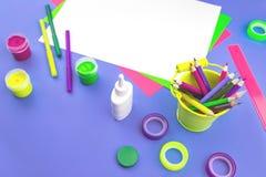 Mesa violeta brilhante com artigos de papelaria de néon sortidos foto de stock royalty free