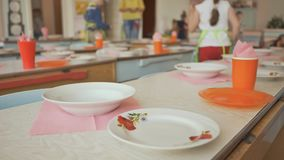 Mesas de jantar com placas, canecas, forquilhas e colheres no jardim de infância Preparação para uma pausa para o almoço por uma  filme