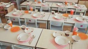 Mesas de jantar com placas, canecas, forquilhas e colheres no jardim de infância Preparação para uma pausa para o almoço Tabele o video estoque