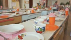 Mesas de jantar com placas, canecas, forquilhas e colheres no jardim de infância Preparação para uma pausa para o almoço Tabele o filme