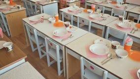 Mesas de jantar com placas, canecas, forquilhas e colheres no jardim de infância Preparação para uma pausa para o almoço Tabele o vídeos de arquivo