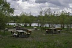 Mesas de picnic cerca de un río fotografía de archivo
