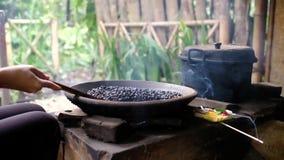 Mescolando i chicchi di caffè crudi in padella nel vecchio modo tradizionale a mano video d archivio