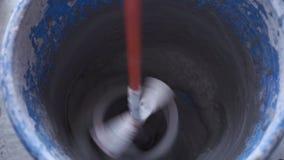 Mescolando la miscela con un miscelatore su un trapano - movimento lento archivi video