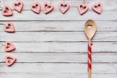 Mescolatura del cucchiaio su un fondo bianco, cuori rosa immagini stock libere da diritti