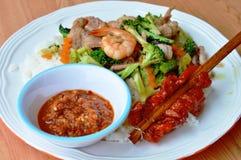 Mescoli i broccoli fritti con frutti di mare e carne di maiale e la pelle grigliata del pollo in bastone di legno Fotografia Stock