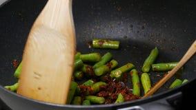 Mescoli i fagioli di lunghezza fritti dell'iarda, le spezie, pasta di curry archivi video