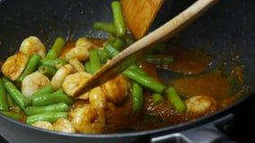 Mescoli il gamberetto fritto, i fagioli di lunghezza dell'iarda, le spezie, pasta di curry video d archivio