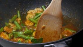 Mescoli il gamberetto fritto, le foglie della calce del kaffir, i fagioli di lunghezza dell'iarda, le spezie, pasta di curry video d archivio