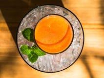 Mescoli il succo del fruite in vetro con ghiaccio messo sulla tavola di legno Fotografia Stock