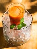 Mescoli il succo del fruite in vetro con ghiaccio messo sulla tavola di legno immagini stock libere da diritti