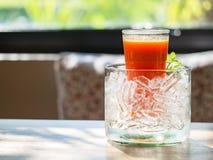 Mescoli il succo del fruite in vetro con ghiaccio messo sulla tavola di legno fotografie stock