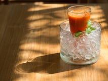 Mescoli il succo del fruite in vetro con ghiaccio messo sulla tavola di legno fotografia stock libera da diritti