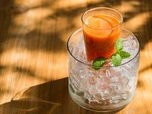 Mescoli il succo del fruite in vetro con ghiaccio messo sulla tavola di legno Immagini Stock