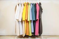 Mescoli la fila di colore dei cappotti femminili sui ganci Fotografia Stock Libera da Diritti