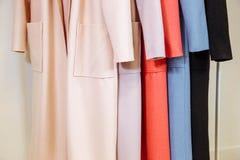 Mescoli la fila di colore dei cappotti femminili sui ganci Fotografia Stock
