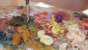 Mescoli la pittura a olio di colori marroni e verdi sulla tavolozza Movimento lento, primo piano stock footage