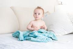 9 meses adorables del bebé que se sienta en cama después de lavarse en baño Imagen de archivo