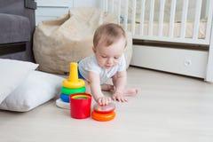 10 meses adorables del niño pequeño p que pone en juegos del educaitonal en piso Fotografía de archivo libre de regalías