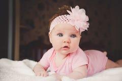 3 meses bonitos do bebê idoso no rosa que encontra-se para baixo em uma cama branca em casa Olhos abertos grandes Dormida infanti Imagem de Stock