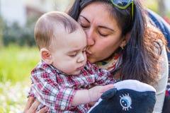 6 meses bonitos do bebê que recebe o beijo pelo mum Fotografia de Stock Royalty Free