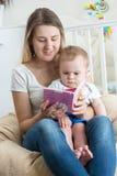 10 meses de assento de assento do bebê idoso com a mãe que lê o livro Fotografia de Stock Royalty Free