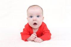 3 meses de bebé en el mono rojo que miente en el vientre Imagen de archivo libre de regalías