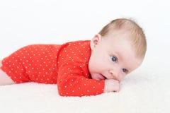 2 meses de bebé en el mono rojo que miente en el vientre Imágenes de archivo libres de regalías