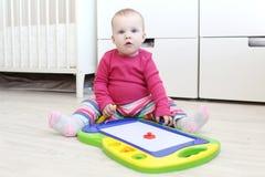 10 meses de bebé que pinta el tablero del dibujo de los niños magnéticos en Foto de archivo
