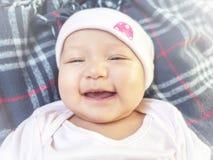 4 meses de bebé que ríe a la cámara Pequeño gilr alegre en mono rosado y sombrero que pone en la cama que ríe a su madre imagen de archivo