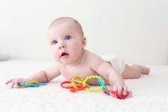 4 meses de bebê com teether educacional do brinquedo em casa Imagem de Stock Royalty Free