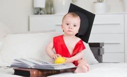 10 meses de bebê idoso no tampão da graduação que senta-se no sofá com livros Foto de Stock Royalty Free