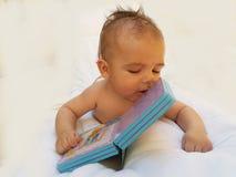 3 meses de bebê idoso que joga com livro Imagens de Stock