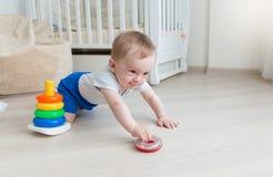 9 meses de bebê idoso que joga com a torre do brinquedo na sala de visitas imagens de stock royalty free