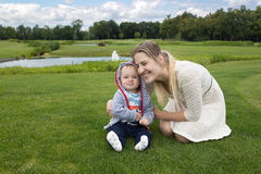 9 meses de bebê idoso que senta-se na grama no parque com seu beautifu Fotos de Stock Royalty Free