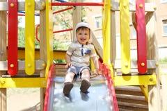 20 meses de criança que desliza no campo de jogos Fotografia de Stock Royalty Free