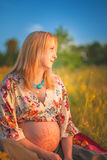 9 meses de mujer embarazada que se sienta en hierba amarilla y la sonrisa Para bebé que espera Concepto del embarazo Imagen de archivo libre de regalías