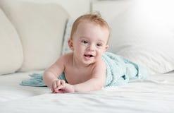 9 meses del bebé debajo de la toalla azul que miente en el sofá en r de vida Imagen de archivo libre de regalías