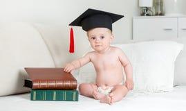 10 meses del bebé en el sombrero del birrete que se sienta con la pila de libro Fotografía de archivo libre de regalías