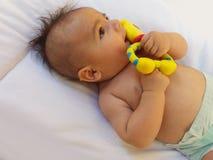 3 meses del bebé que juega con el juguete de la dentición Fotos de archivo libres de regalías