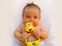 3 meses del bebé que juega con el juguete de la dentición Fotografía de archivo