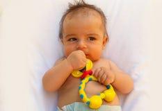 3 meses del bebé que juega con el libro Imagen de archivo