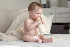 9 meses del bebé que se sienta en cama y la leche de consumo del bott Imagen de archivo libre de regalías