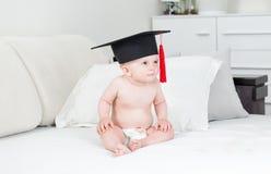 10 meses del bebé que se sienta en el sofá y la graduación que lleva Ca Imágenes de archivo libres de regalías