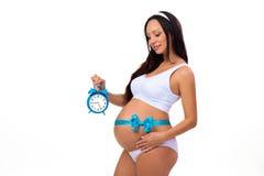 9 meses Embarazo feliz Mujer embarazada con el despertador en sus manos y arco azul en la panza Fotografía de archivo
