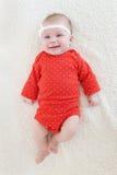 2 meses felices de bebé en mono rojo Fotos de archivo