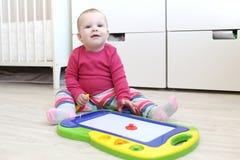 10 meses lindos de bebé con el tablero del dibujo de los niños magnéticos a Imágenes de archivo libres de regalías
