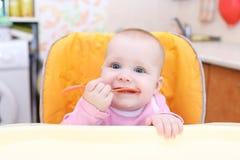 7 meses lindos de bebé con la silla del bebé del spoonon en cocina Foto de archivo libre de regalías